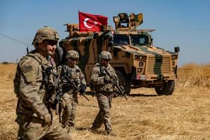 In a photo from Sept 8, 2019, US troops walk past a Turkish military vehicle during a joint patrol with Turkish troops in the Syrian village of al-Hashisha on the outskirts of Tal Abyad town along the border.