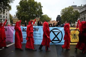 Climate change activists from the group Extinction Rebellion, dressed in red costumes, parade past colleagues as they block Whitehall with banners in central London, on Oct 7, 2019.