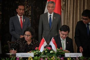 Indonesian President Joko Widodo and Prime Minister Lee Hsien Loong witness as Indonesian Minister of Finance Sri Mulyani Indrawati and Finance Minister Heng Swee Keat sign a memorandum of understanding during the Singapore-Indonesia Leaders' Retre