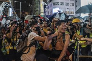 Above: A masked man attacking another man in Kowloon on Sunday, in front of journalists. In recent weeks, some protesters have targeted property and individuals with greater ferocity. Left: Protesters setting fire to an entrance of the Admiralty MTR