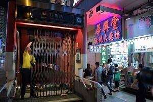 An MTR employee slides a gate at an entrance of Mong Kok train station during a media tour in Hong Kong on Oct 8, 2019.