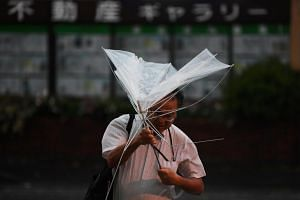A man with an umbrella crosses a street under the rain as a typhoon hits Tokyo, on Sept 9, 2019.