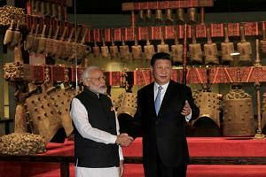 In this picture taken on April 27, 2018, Indian Prime Minister Narendra Modi (left) and Chinese President Xi Jinping shake hands as they visit the Hubei Provincial Museum in Wuhan, Hubei province, China.
