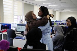Employees of Utusan Malaysia in tears after the cash-strapped publisher went bust and laid off all staff yesterday. PHOTO: REUTERS