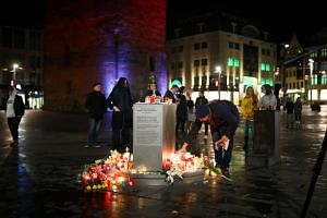 A man puts a candle at the central market square in Halle, Germany, on Oct 9, 2019, after two people were killed in a shooting in front of a synagogue.