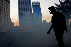 An anti-government protester is silhouetted against the skyline during a demonstration near Central Government Complex in Hong Kong on Sept 15, 2019.