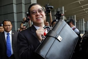 Malaysia's Finance Minister Lim Guan Eng with a briefcase containing the 2020 Budget documents in Putrajaya on Oct 11, 2019.