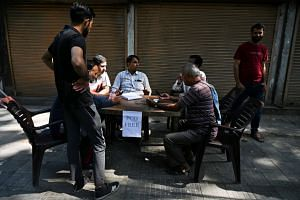 A photo taken on Sept 3, 2019, showing men gathering to make calls at a makeshift phone booth set up by Indian security forces in Srinagar.