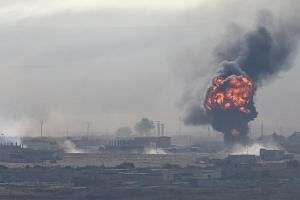 An explosion is seen over the Syrian town of Ras al Ain on Oct 12, 2019. The town centre of the border town was seized by Turkish-backed Syrian rebels, according to a senior Turkish security official.