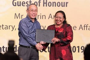 Commissioner of Prisons Desmond Chin presenting an award to Ms Kasmawati Kali Ubi as part of the Yellow Ribbon Celebrating Second Chances Awards Ceremony on Oct 12, 2019.