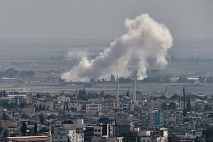 Smoke rises from the Syrian town of Ras al-Ain, in a picture taken from the Turkish side of the border in Ceylanpinar on Oct 11, 2019, on the third day of Turkey's military operation against Kurdish forces.