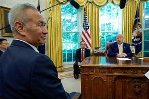 Chinese Vice-Premier Liu He sitting across a desk from US Presdient Donald Trump in the Oval Office on Oct 11, 2019.