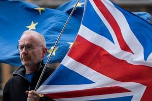 An anti-Brexit activist holds a United Kingdom flag next to a European flag in front of the EU headquarters in Brussels on Oct 11, 2019.