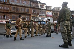 Indian police officers stand at the site of a grenade attack in Srinagar on Oct 12, 2019.