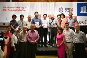 Deputy Prime Minister Heng Swee Keat and People's Action Party Seniors Group (PAP.SG) chairman Tan Chuan-Jin with the PAP.SG Ambassador Handbook, during an event to mark the International Day of Older Persons on Oct 13, 2019.