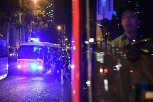 A driver watches from his bus as Hong Kong police officers board their van on Oct 13, 2019.