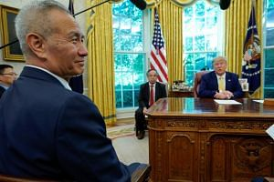 A photo taken on Oct 11 shows Chinese Vice-Premier Liu He and US President Donald Trump during a meeting in the Oval Office of the White House in Washington.