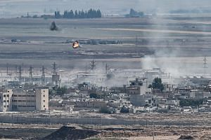 Smoke rising in the Syrian border town of Ras al-Ain following a Turkish offensive against the Kurdish People's Protection Units, on Oct 13, 2019.