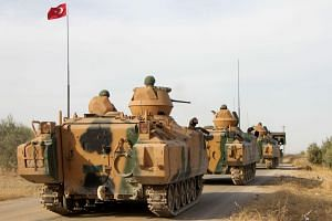Turkish soldiers are transported in armoured personnel carriers through the town of Tukhar, north of Syria's northern city of Manbij near the Turkish border on Oct 14, 2019.