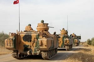 Turkish soldiers are transported in armoured personnel carriers through the town of Tukhar, north of Syria's northern city of Manbij, on Oct 14, 2019, as Turkey and it's allies continues their assault on Kurdish-held border towns in northeastern Syri