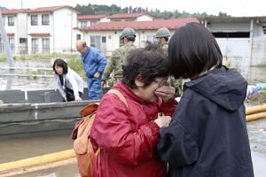 A woman cries in relief after being rescued from an area flooded by Typhoon Hagibis in Marumori, Miyagi prefecture, on Oct 14, 2019.