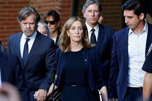In a photo taken on Sept 13, 2019, actress Felicity Huffman leaves the federal courthouse with her husband William H Macy in Boston, Massachusetts.