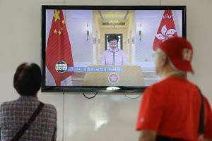 Shoppers watch as Hong Kong Chief Executive Carrie Lam delivers her third policy address via video after her session at the legislative council was disrupted by heckling pro-democracy lawmakers in Hong Kong on Oct 16, 2019.