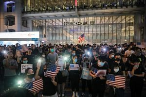 Protesters holding up lighted mobile phones and US flags in Hong Kong, on Oct 14, 2019.