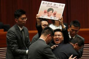 A lawmaker being ejected from the Legislative Council on Oct 17 as he shouts at Chief Executive Carrie Lam and waves a placard showing her with blood on her hands from recent violent protests in Hong Kong.