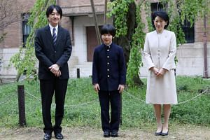 In a picture taken on April 8, 2019, Prince Hisahito (centre), accompanied by his parents Prince Akishino and Princess Kiko, poses for photos at Ochanomizu University junior high school in Tokyo, Japan. He is second in line to the throne.
