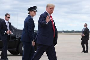 US President Donald Trump gestures to the media as he departs Washington for campaign travel to Texas from Joint Base Andrews, Maryland, US, on Oct 17, 2019.