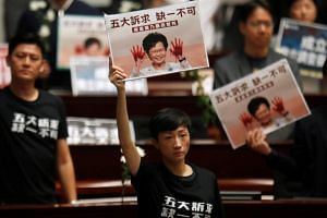 Hong Kong lawmakers hold protest signs in the Legislative Council. Beijing's local allies in Hong Kong don't agree on much, and their differences are even deeper on the protesters' biggest demand: greater democracy.