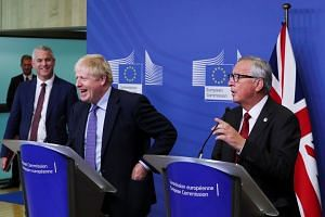 Britain's Brexit Secretary Stephen Barclay, Prime Minister Boris Johnson and European Commission President Jean-Claude Juncker at a news conference after clinching the Brexit deal in Brussels, Belgium, on Oct 17, 2019.