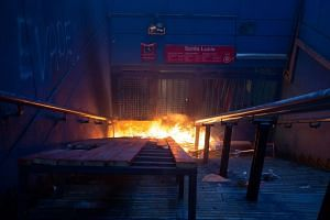 A fire set by protesters burns at an entrance to Santa Lucia metro station in Santiago, Chile, on Oct 18, 2019.
