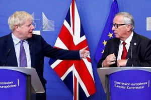 British Prime Minister Boris Johnson and European Commission President Jean-Claude Juncker during a news conference after clinching the Brexit deal at the sidelines of the European Union leaders summit in Brussels, Belgium, on Oct 17, 2019.