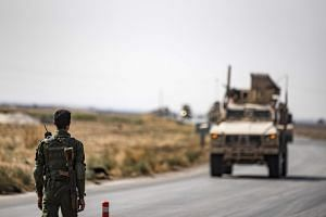 A fighter from the Syrian Democratic Forces stands guard as a convoy of US military vehicles drives on a road after US forces pulled out of their base in the Northern Syrian town of Tal Tamr on Oct 20, 2019.