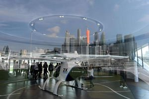 Visitors viewing the Volocopter unmanned air taxi transport displayed ahead of the 26th Intelligent Transport Systems World Congress in Singapore, on Oct 21, 2019.