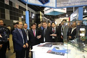Coordinating Minister for Infrastructure and Minister for Transport Khaw Boon Wan (front, second from left) touring the Intelligent Transport Systems World Congress' exhibition yesterday at the Suntec Singapore Convention and Exhibition Centre. ST PH