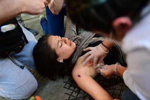 A woman being assisted after she was shot with a rubber bullet during clashes with riot police in Santiago, on Oct 21, 2019.