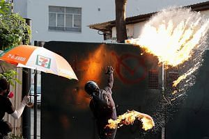 A protester throwing a petrol bomb at Tsim Sha Tsui Police Station during a rally on Sunday. Hong Kong has been riven by seething protests for the past 20 weeks, with violence spiralling on both sides of the ideological divide. PHOTO: REUTERS