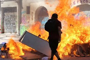Protesters set a barricade on fire in capital Santiago, which has been placed in a state of emergency and under a night curfew, on Oct 22, 2019.