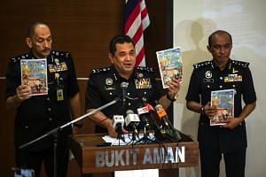 Bukit Aman Criminal Investigation director Datuk Huzir Mohamed (centre) holds up a copy of the controversial comic book while speaking during a media conference in Kuala Lumpur on Oct 23, 2019.