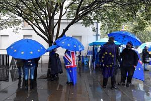 Anti-Brexit and pro-EU protesters shelter from the rain outside the Houses of Parliament in London on Oct 24, 2019.