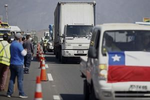 People demonstrate with their cars, trucks, and taxis on the Route 5 North in Santiago.