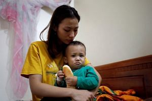 Ms Hoang Thi Thuong, wife of possible victim Nguyen Dinh Tu, with her son at their home in Nghe An province, Vietnam. She lost contact with her husband on Oct 21.