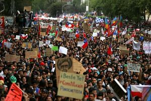 Demonstrators march with flags and signs during a protest against Chile's state economic model in Santiago, Chile, on Oct 25, 2019.