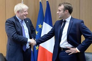 Britain's Prime Minister Boris Johnson and French President Emmanuel Macron during a European Union leaders summit in Brussels on Oct 17, 2019.