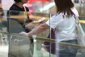 A go-between (right) with a maid after handing money over to her outside a telco shop at AMK Hub, with instructions on which mobile subscription plan to sign up for. ST PHOTO: SHINTARO TAY