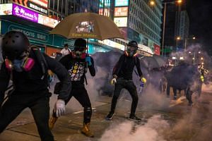 Pro-democracy protesters react after police fired tear gas in the Mong Kok district in Hong Kong, on Oct 27, 2019.