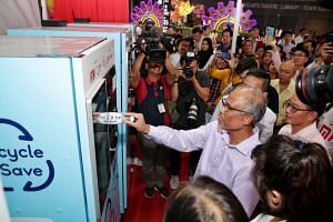 Environment and Water Resources Minister Masagos Zulkifli trying out the reverse vending machine during its launch at Our Tampines Hub on Oct 31, 2019.